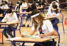 Študenti, ki nosijo maske in ščiti, sodelujejo na sprejemnem izpitu na fakulteti v Saleu v Maroku, 3. julija 2020.
